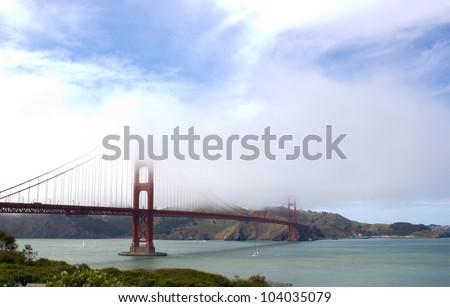Golden Gate Bridge partially hidden by haze - stock photo