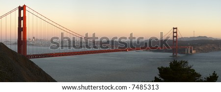 Golden Gate Bridge (San Francisco, California) lit by the rays of setting sun against a backdrop of downtown and sky glowing with orange and red hues. - stock photo