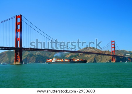 golden gate bridge seen during the afternoon showing a huge cargo ship crossing underneath it