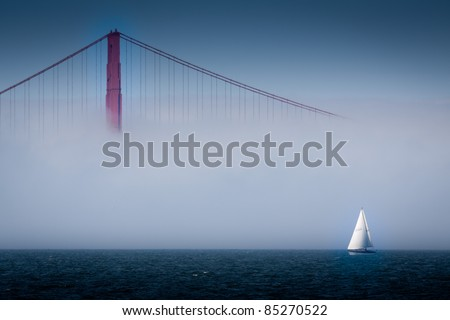 Golden Gate Bridge Shrouded in Fog with Sailboat in San Francisco Bay - stock photo