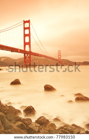 Golden Gate bridge with beautiful stone in the foreground and cloud like ocean wave. San Francisco, USA - stock photo