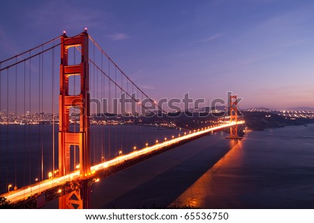 Golden Gate Bridge with San Francisco city in the background at twilight with light trail from the car on the bridge - stock photo