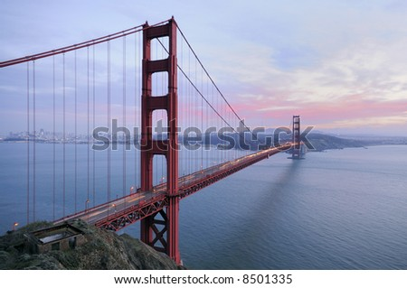 Golden Gate Brige with sunset colors in the background and ruins of old fortification in the foreground. Copyspace on the right.