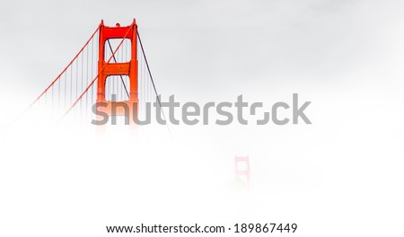 Golden Gate surrounded by fog - stock photo