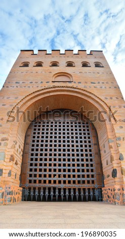 Golden Gates in Kiev, capital of Ukraine. Powerful tall ancient gate of wooden beams, paneled with metal plates with sharp spines located in wall of stone citadel with crenellated fortifications - stock photo