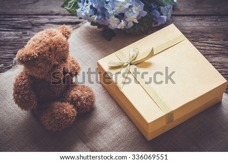 Golden gift box and teddy bear, Vintage color tone - stock photo