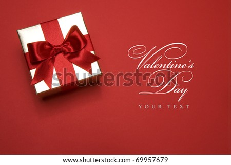 golden gift box with a red bow on red background - stock photo