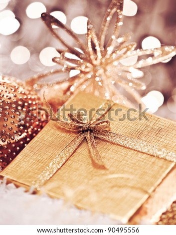 Golden gift box with baubles decorations, Christmas tree ornament for winter holidays, present with abstract bokeh shiny glowing blur lights background