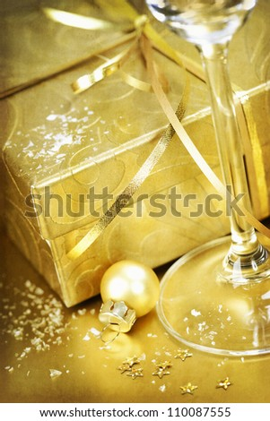 Golden gift box with golden ribbon and champagne