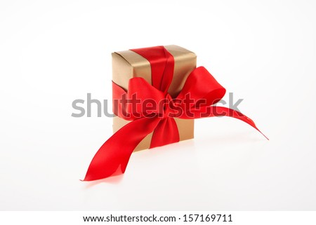 Golden gift box with red large ribbon - stock photo