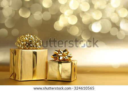Golden gift boxes on abstract background - stock photo