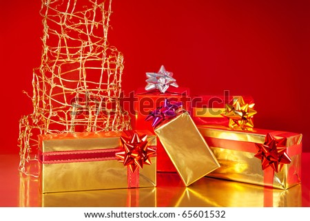 Golden gift boxes under a modern Christmas tree, on red background