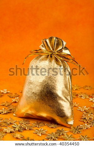 Golden gift sack and golden snowflakes over orange background - stock photo