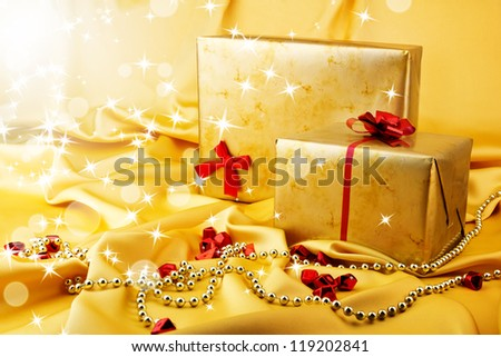 Golden gift with red bow on silk with rays and star. Christmas background - stock photo