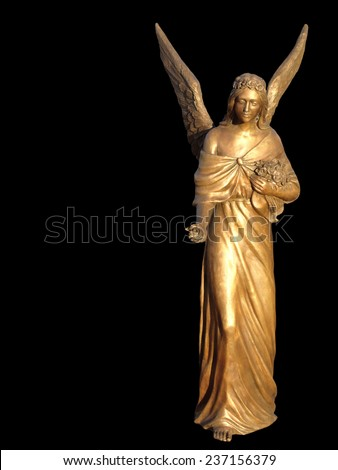 Golden gilt metal statuette or sculpture of a celestial angel with raised wings holding a bouquet of flowers with her hand held out in offering over a black background with copyspace - stock photo