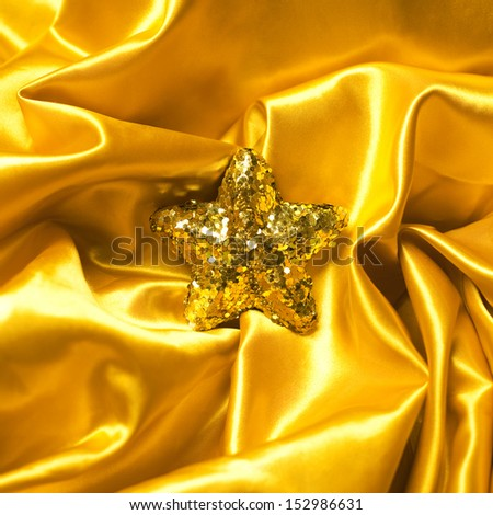 Golden glamour theme with sparkling christmas star on wavy golden atlas (satin) background. Studio shot