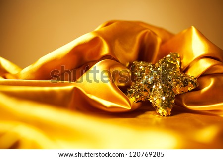 Golden glamour theme with sparkling christmas star over light brown background. Studio shot