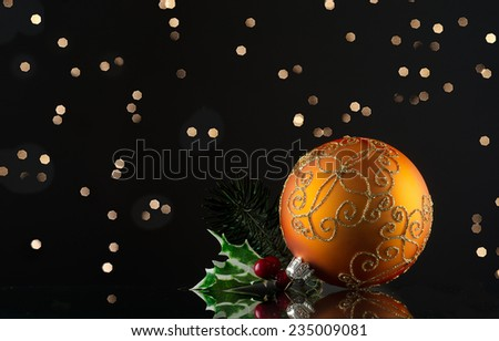 Golden glass ornament for Christmas on a reflective surface, Bokeh lights on the background - stock photo