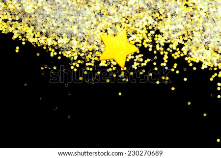 golden glitter and star on black - stock photo