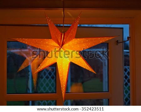 Golden glittering star shaped Christmas paper ornament hanged as festive decoration - stock photo