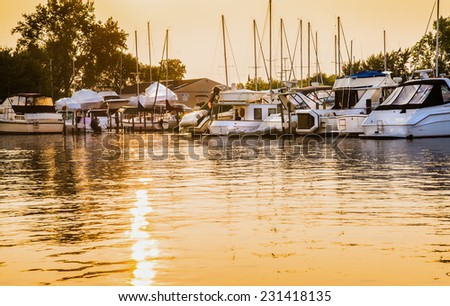 Golden glow on marina boats and water - stock photo