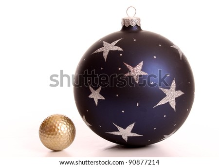 Golden golf ball and a Christmas bauble - stock photo