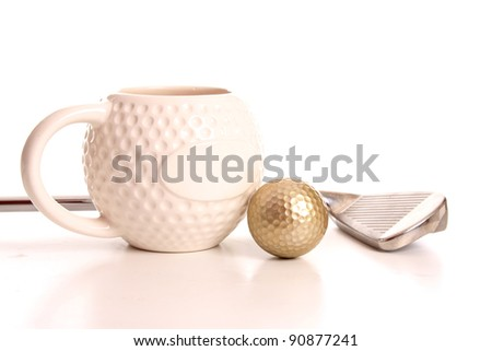 Golden golf ball and club laying next to a golf cup