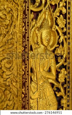 Golden guardian sculpture at Senesukharam Buddhist temple in Luang Prabang, Lao - stock photo