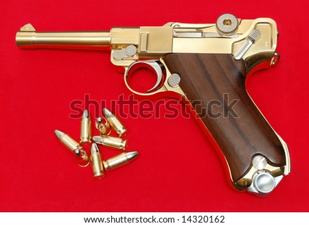 Golden gun isolated over a red background