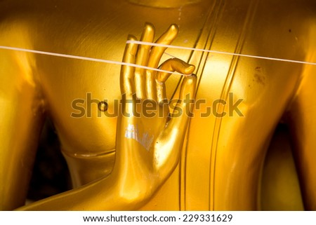 Golden hand of image Buddha close up. - stock photo