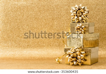 Golden Holidays Decoration. Gifts With Ribbon Bow On Shiny Background - stock photo