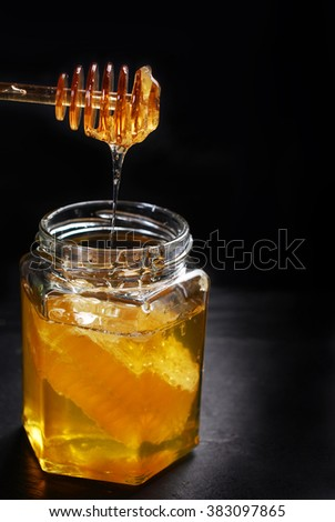 golden honey dripping from spoon into glass jar with comb on black background  with space for own text  - stock photo