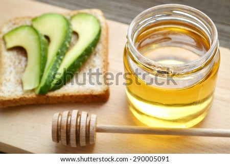 Golden honey with honeystick and a healthy sandwich with green avocado on wooden board - stock photo