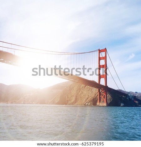 Golden hour view of the Golden Gate Bridge in San Francisco, California from the water in the bay