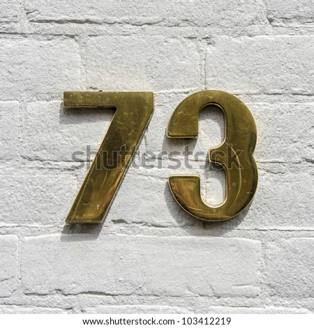 golden house number seventy-three on a white painted brick wall - stock photo