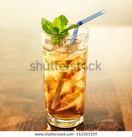 golden iced tea with blue straw and mint - stock photo