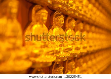 golden Image buddhas lined up along the wall of buddhist temple - stock photo