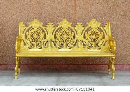golden iron bench on brown cement wall - stock photo