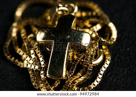 golden jewelry cross with necklace on black ground - stock photo