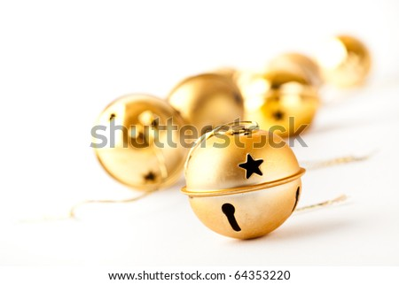 Golden jingle bell Christmas baubles on white - stock photo