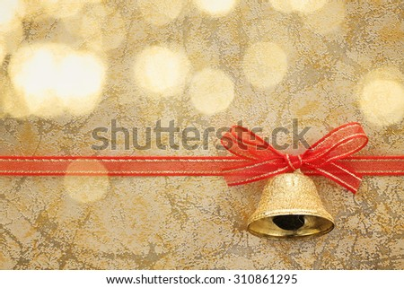 Golden jingle bell with ribbon bow on festive background - stock photo