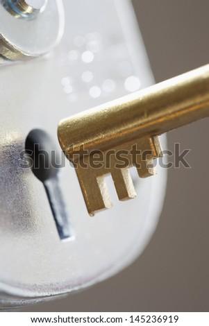 Golden key and padlock close-up - stock photo