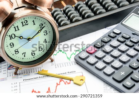 Golden key with a clock, a calculator and an abacus over business and financial summary reports. Key success in sustainable growth investment concept. - stock photo