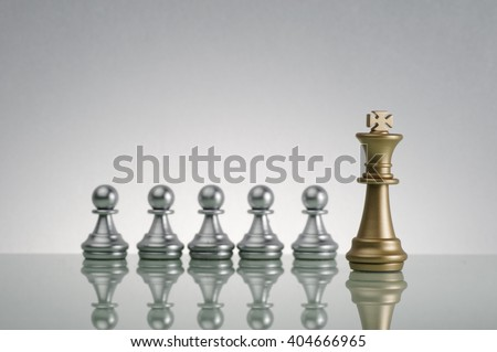 Golden King and silver pawn on chess game - Leadership Concept - stock photo