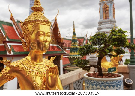 Golden Kinnari statue at Temple of Emerald Buddha (Wat Phra Kaew) in Grand Royal Palace. Half-bird, half-woman creature at south-east Asian Buddhist mythology. Bangkok, Thailand - stock photo