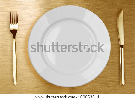 Golden knife, fork and white plate