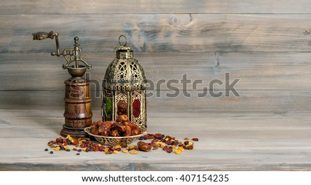 Golden lantern and vintage mill. Raisins and dates fruits on wooden background. Oriental arabic decoration - stock photo