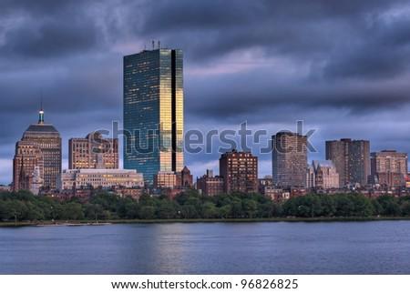 Golden light illuminated the Boston Skyline viewed over the Charles River - stock photo
