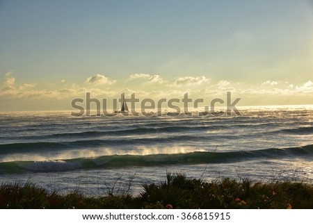 Golden light over the ocean, with steam rising on a cold morning. - stock photo
