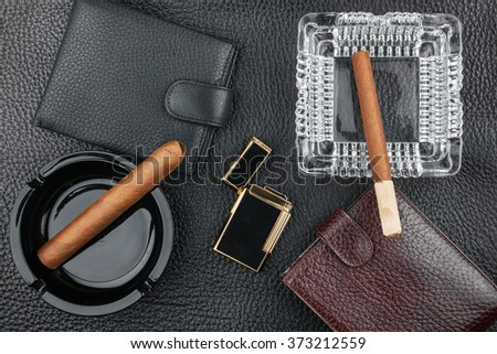 Golden lighter with cigar and purse lying on a black skin, can be used as background - stock photo